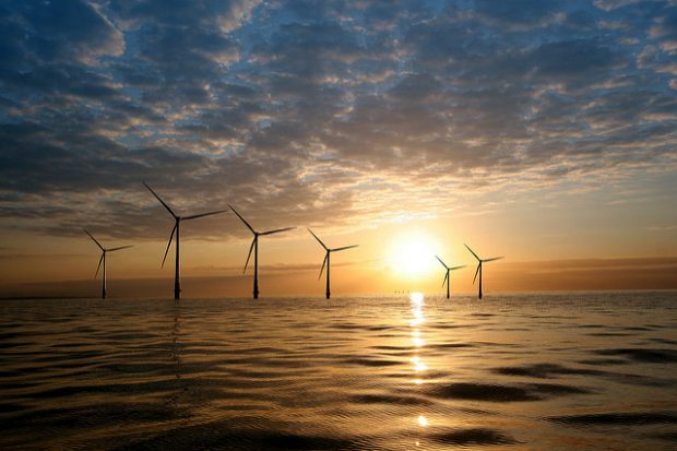 Wind turbines at sea with a sunset.