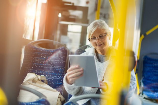 Older lady on bus using a tablet device